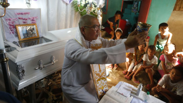 The mother of the slain girl Myka Ulpina sprinkles holy water at her coffin during a mass.