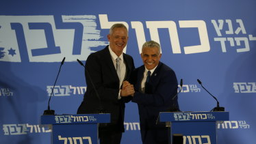 Retired Israeli military chief Benny Gantz, left, smiles with Yair Lapid, head of the Yesh Atid party.