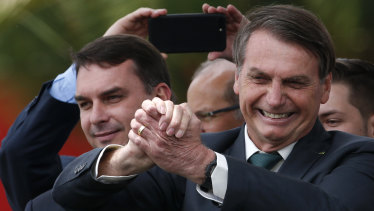 Accompanied by his son Senator Flavio Bolsonaro, left, Brazilian President Jair Bolsonaro flashes a victory clasp at the launch of his new political party, Alliance for Brazil, in Brasilia.