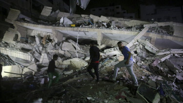 Owners of stores at the building inspect the damage of their destroyed multi-story building in Gaza City.