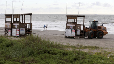 Park board crews move the lifeguard towers off the beach in Galveston, Texas.