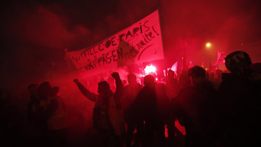 Flares illuminate the darkness at the end of a demonstration in Paris.
