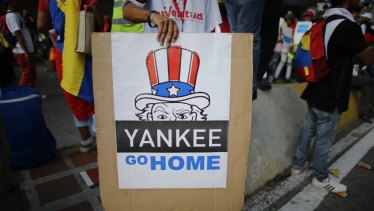 "A supporter of President Nicolas Maduro holds a ""Yankee go home"" sign  in Caracas, Venezuela."