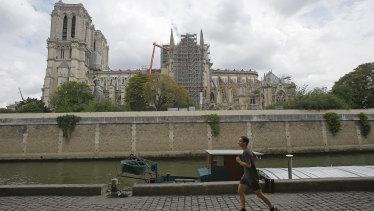 A man jogs along the Seine River near Notre-Dame.