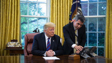 A White House aide assists US President Donald Trump connect a phone call in the Oval Office.