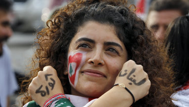 """An anti-government protester displays the words """"Revolution"""" left, and """"Lebanon"""" right, in Arabic on her hands."""