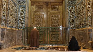 A cleric and a woman pray behind a closed door of the Fatima Masumeh shrine in Qom, Iran.
