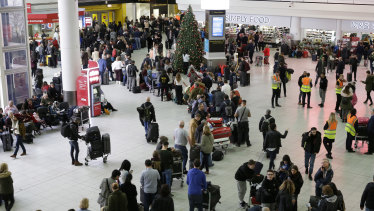 People queue at Gatwick airport, near London on Thursday.