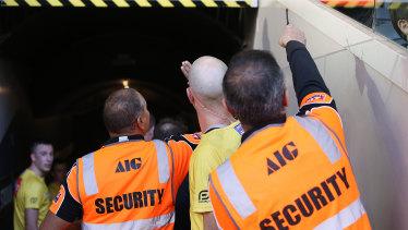 "Umpire Mathew Nicholls and ""hi-vis"" security staff at the Carlton v Brisbane game at Marvel Stadium this month."