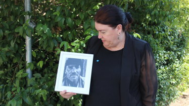 Mark Russell's sister Julie Ann Stewart looks at a photo of him outside the NSW Coroners Court.
