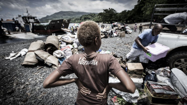 A young boy watches his family unload their possessions.