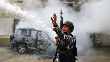 A Lebanese policeman gestures to firefighters as they extinguish a police car that was set on fire by anti-government protesters in the northern city of Tripoli, Lebanon.