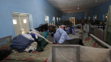 People inspect belongings of missing Government Science Secondary School student at their hostel in Kankara, Nigeria.