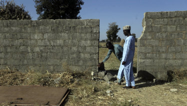 People inspect a wall and metal door broken by the gunmen who kidnapped Government Science Secondary School students in Kankara.