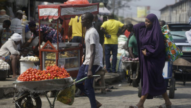 People walk, in a market in Lagos, Nigeria.