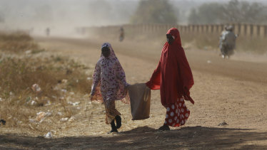Two women walk past the Government Science Secondary School in Kankara on Tuesday.
