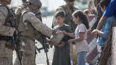 A US Marine opens a meal ready-to-eat package for children during an evacuation at Hamid Karzai International Airport in Kabul.