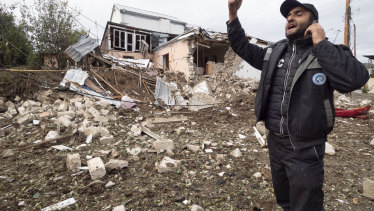 A man speaks on the phone near a house destroyed by shelling by Azerbaijan's artillery in Stepanakert, self-proclaimed Republic of Nagorno-Karabakh.