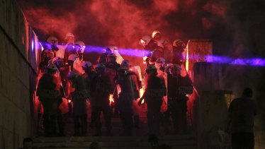 A flare thrown by protesters highlights riot police guarding the parliament during a demonstration against the agreement between Greece and Macedonia over a dispute of the former Yugoslav\'s republic name, in Athens, on Saturday.