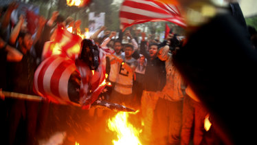 Iranian demonstrators burn representations of the US flag during a protest in front of the former US Embassy in response to President Donald Trump's decision Tuesday to pull out of the nuclear deal and renew sanctions, in Tehran, Iran.