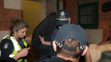 Police direct Mr Basham outside Bairnsdale Magistrates Court.