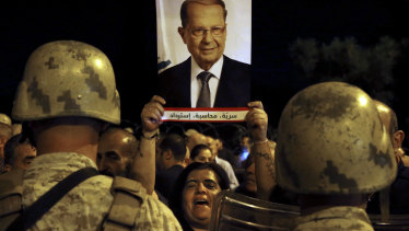 A supporter of Lebanese President Michel Aoun holds up his picture during a protest near the presidential palace in Beirut on Tuesday.