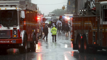 First responders arrive near the scene where a helicopter crash-landed on the roof a midtown Manhattan skyscraper.