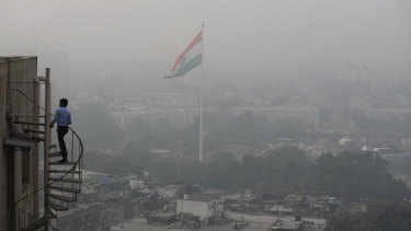 A man climbs to the top of a Delhi building as the city is enveloped in smog and dust on Friday.