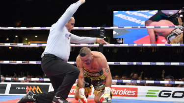Down and out: Referee Phil Austin waves off the fight with Anthony Mundine unable to find his feet.