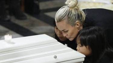 The widow of French rocker Johnny Hallyday, Laeticia Hallyday, and her children, Jade, left, and Joy, kiss Johnny Hallyday's coffin at his 2017 funeral.