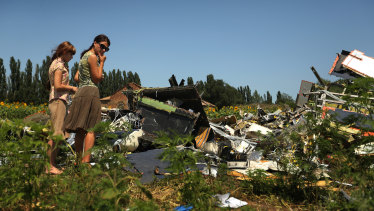 Women look at the debris of downed Malaysian flight MH17 cockpit site on the outskirts of Rassypnoye village in the self proclaimed Donetsk People's Republic, East Ukraine.