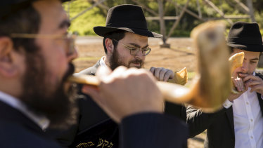Members of the Jewish community blow on shofars during the ceremony at Rookwood Cemetery.