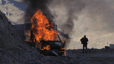 A man stands near his burning car which caught on fire during the climb along the road to a mountain pass, near the border between Nagorno-Karabakh and Armenia.