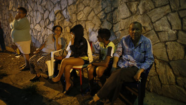 Evacuated residents sit outside their apartments in a street near the leaning tower.