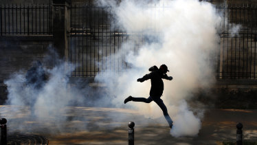 An activist kicks a tear canister gas shot by riot police during a Paris protest in support of the French railway employees.