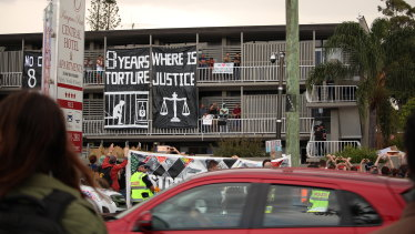 Protesters join below as some men protest on the Kangaroo Point hotel balcony in August.