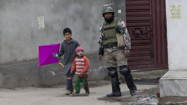Kashmiri children walk past an Indian paramilitary soldier in Srinagar, Indian-controlled Kashmir.