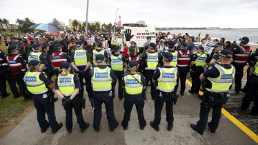 Police stand between far-right and anti-racism protesters at the St Kilda rally.