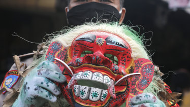 A police officer holding a Balinese traditional mask, called celuluk, portrays the coronavirus during a campaign to get people wear masks.