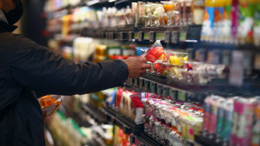 A shopper takes a product off a shelf at an Amazon Fresh cashierless convenience store.