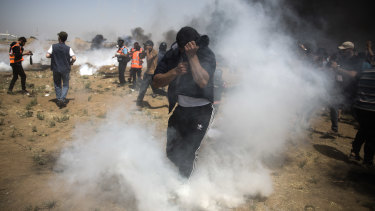 Palestinian protesters run for cover from teargas fired by Israeli troops during fresh demenstrations in which medics said four people died.
