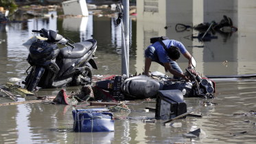 A man tries to get his motorbike upright at a tsunami-devastated area in Talise beach, Palu.