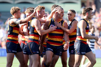 Taylor Walker is congratulated by teammates after scoring in the Crows' win over Geelong.