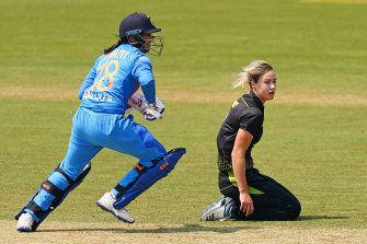 India's Smriti Mandhana, left, runs between the wickets as Australian bowler Ellyse Perry, right, looks on.