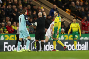 Sheffield United's Chris Basham sees yellow after his red card is overturned by VAR.