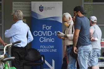 People wearing face masks walk past the sign for the COVID-19 Clinic at St Vincent's Hospital in Darlinghurst, Sydney.