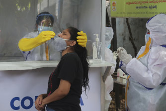 A health worker takes a nasal swab sample to test for COVID-19 in Hyderabad, India.