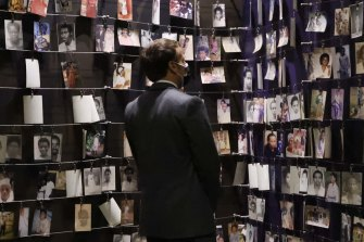 French President Emmanuel Macron looks at the images of genocide victims on display during his visit to the Kigali Genocide Memorial, where some 250,000 victims of the Rwanda massacres are buried, in Kigali.