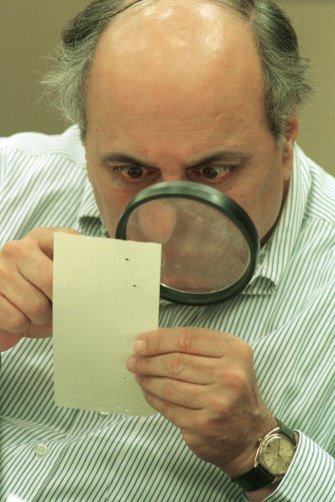 Judge Robert Rosenberg of Broward County Canvassing Board uses a magnifying glass to view a dimpled chad (the bit of paper pushed out when a hole is punched) on a punch-hole ballot in 2000, during a recount of votes in Fort Lauderdale, Florida.