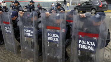 Mexican federal police in riot gear receive instructions at the border crossing between Guatemala and Mexico, in Ciudad Hidalgo, Mexico, on Friday.